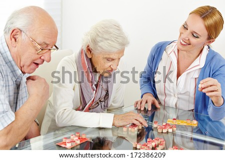 Senior couple playing Bingo with eldercare assistant in nursing home - stock photo
