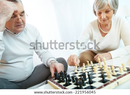Senior couple playing chess at home - stock photo