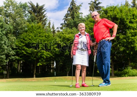 Senior couple playing golf in their leisure time - stock photo