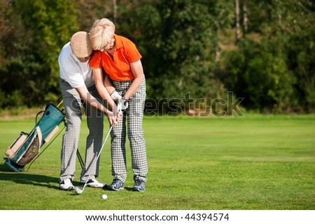 senior couple playing golf on a summer afternoon, the mal partner is trainer to the female golfer - stock photo