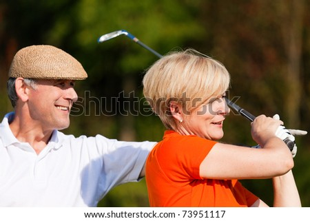 senior couple playing golf on a summer afternoon, the male partner is trainer to the female golfer - stock photo