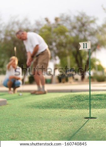 senior couple playing mini golf - stock photo