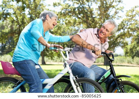 Senior couple playing on children's bikes - stock photo