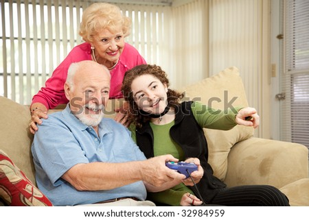 Senior couple playing video games with their teenage granddaughter.