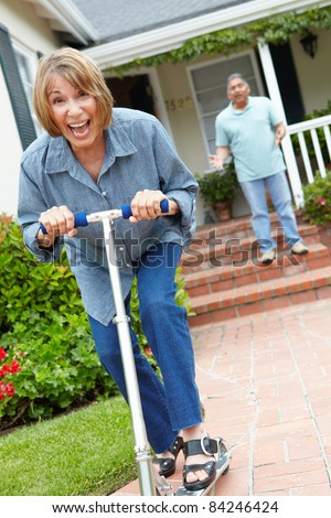 Senior couple playing with children's scooter - stock photo