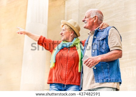 Senior couple pointing a monument during vacation - Active elderly tourist traveling Europe - Concept of  travel lifestyle without age limitation - Warm with soft vintage editing - stock photo