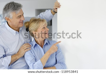 Senior couple pointing at message board - stock photo