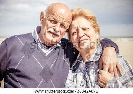 Senior couple portrait - Husband and wife looking at camera and smiling - stock photo