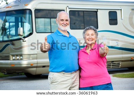 Senior couple posing in front of their luxury motor home, giving a thumbs up. - stock photo