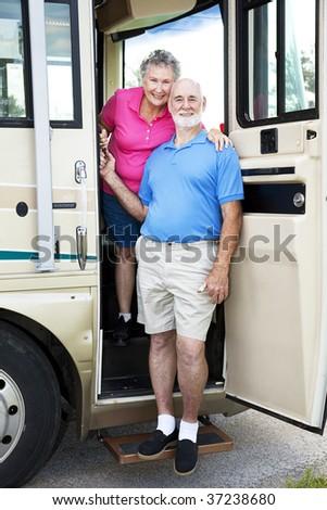 Senior couple posing in the door of their luxury RV. - stock photo