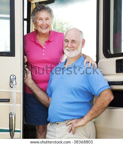Senior couple posing in the doorway of their luxury motor home. - stock photo