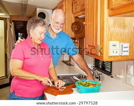 Senior couple preparing a healthy lunch in their motor home kitchen - stock photo