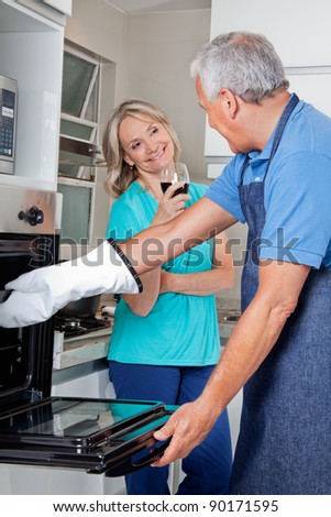 Senior couple preparing food together in home kitchen - stock photo