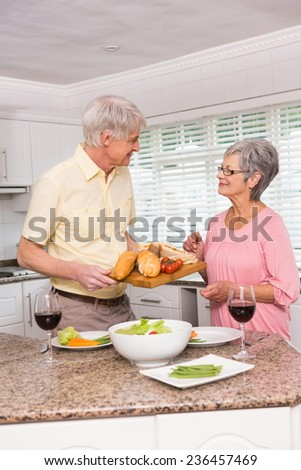 Senior couple preparing lunch together at home in the kitchen - stock photo