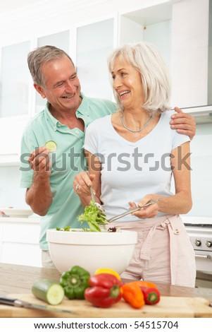 Senior Couple Preparing Salad In Modern Kitchen - stock photo