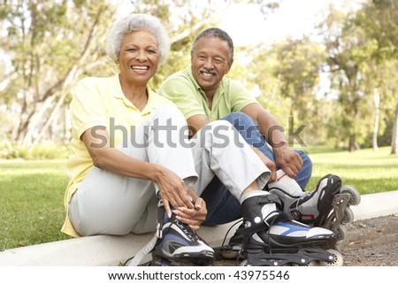 Senior Couple Putting On In Line Skates In Park - stock photo