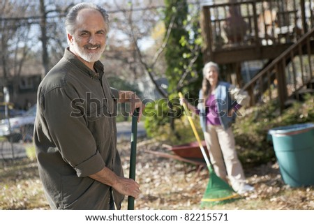Senior couple raking autumn leaves - stock photo