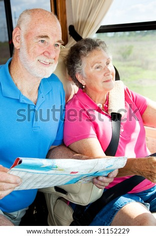 Senior couple reading a map and traveling in their motor home. - stock photo