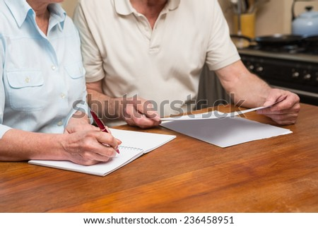 Senior couple reading and writing at home in the kitchen