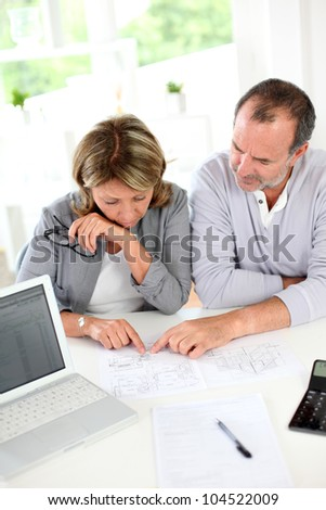Senior couple reading construction plan in office - stock photo