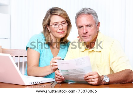 Senior couple reading the bills at new home. - stock photo