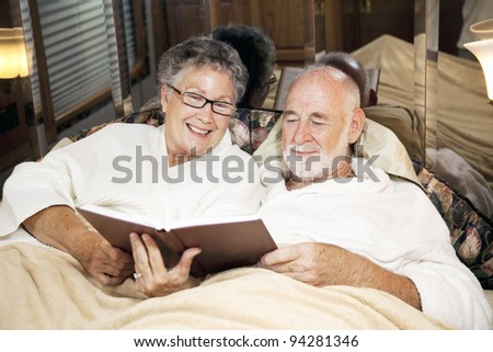 Senior couple reads together at bedtime, in their motor home. - stock photo