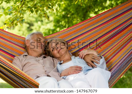 Senior couple relax sleeping together in hammock sunny garden