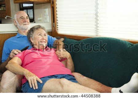 Senior couple relaxes and watches TV on the couch in their motor home. - stock photo