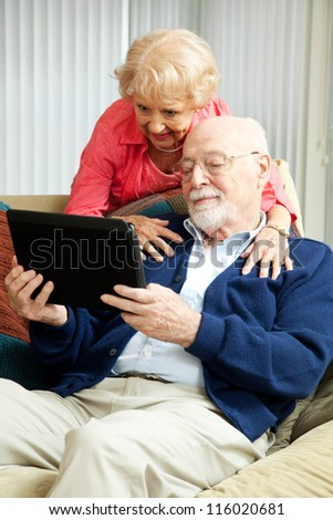 Senior couple relaxing at home, using their tablet PC. - stock photo