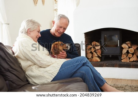 Senior Couple Relaxing At Home With Pet Dog - stock photo