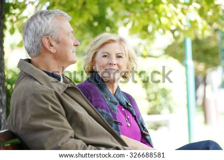 Senior couple relaxing at outdoors. Portrait of smiling elderly woman and friendly old man sitting togetherness at park and relaxing.  - stock photo