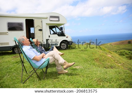 Senior couple relaxing in camping folding chairs, sea landscape - stock photo