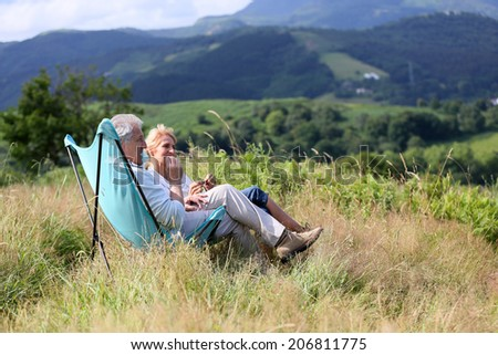Senior couple relaxing in folding chairs in countryside