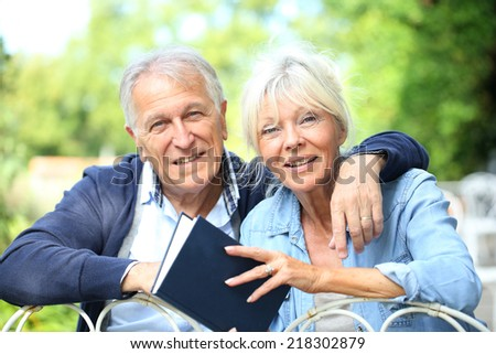 Senior couple relaxing in garden and reading book - stock photo