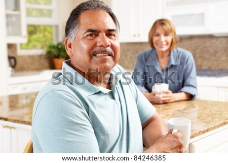 Senior couple relaxing in kitchen - stock photo