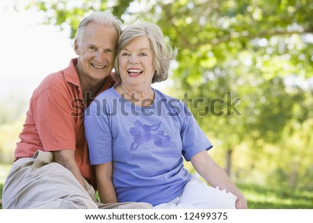 Senior couple relaxing in park sitting on grass - stock photo