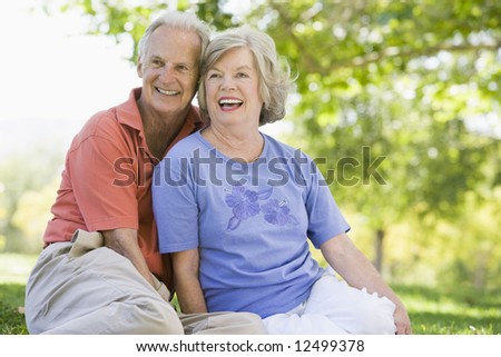 Senior couple relaxing in park sitting on grass