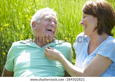 Senior Couple Relaxing In Summer Field Together - stock photo