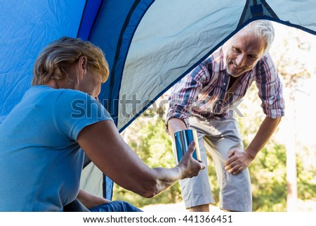 Senior couple relaxing inside their tent in the forest - stock photo