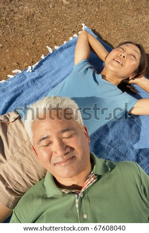 Senior couple relaxing on a blanket outdoors - stock photo