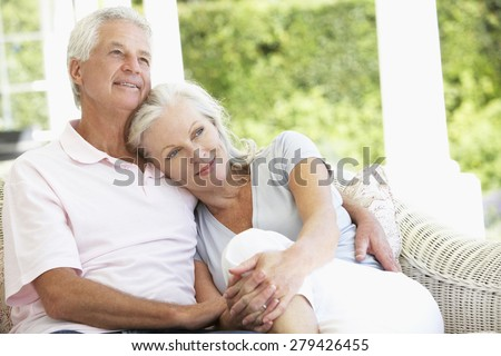 Senior Couple Relaxing On Seat Outside House - stock photo