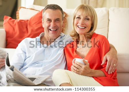 Senior Couple Relaxing On Sofa At Home Reading Newspaper - stock photo