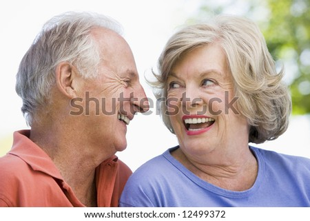 Senior couple relaxing outside in park - stock photo