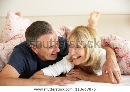 Senior Couple Relaxing Together In Bed - stock photo