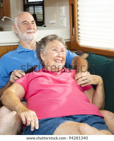Senior couple relaxing together in their travel trailer/ motor home . - stock photo