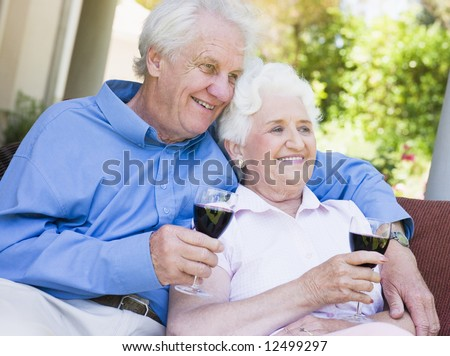 Senior couple relaxing with glass of red wine - stock photo
