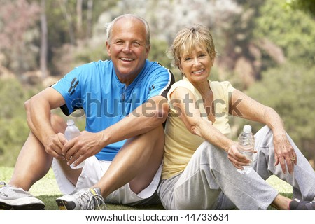 Senior Couple Resting Aftre Exercising In Park - stock photo