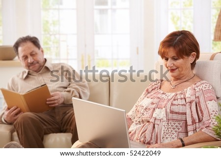 Senior couple resting at home reading book and browsing internet on laptop computer. - stock photo