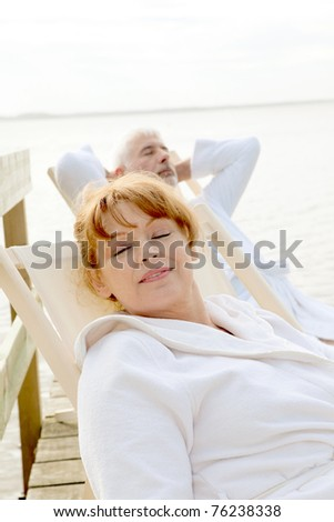Senior couple resting in deckchairs - stock photo