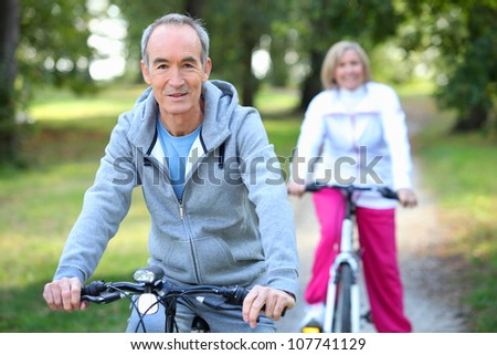 Senior couple riding bikes - stock photo